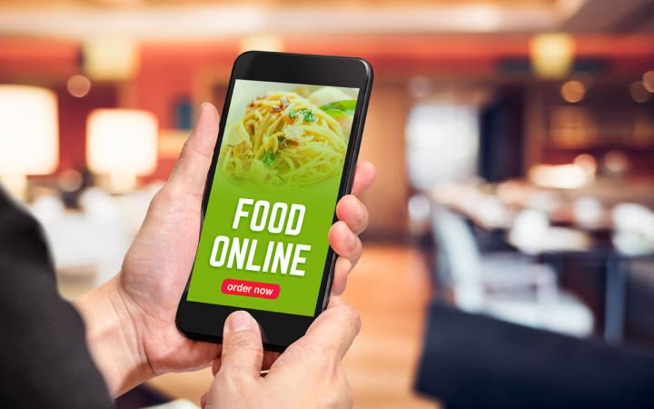 Close up hand holding mobile phone with order food online word on screen.