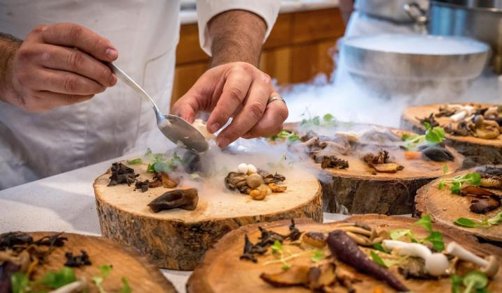 A chef prepares appetizers on wooden blocks.