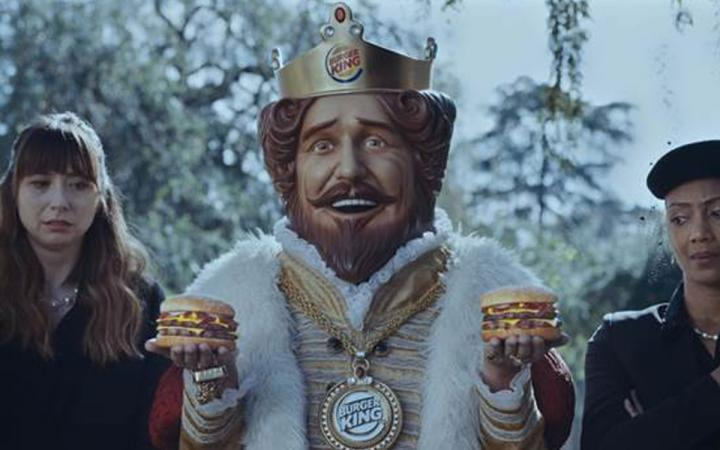 Burger King's mascot holds two burgers at the launch of its new menu item.