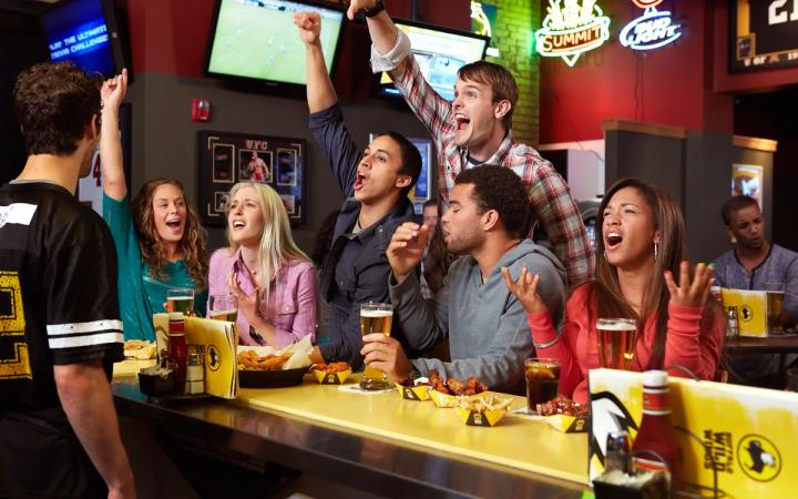 Guests cheer on a sports game at Buffalo Wild Wings.