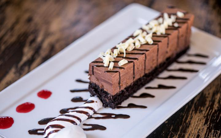Chocolate Mousse Cake on a plate with syrup.