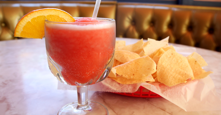 A frozen blood orange margarita in a frosted glass with chips