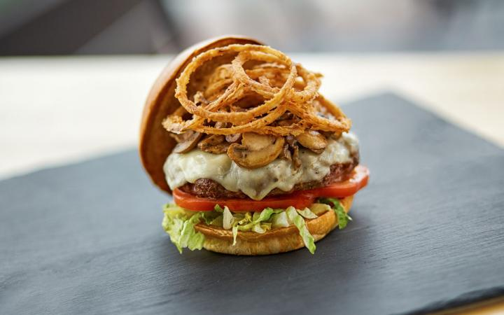 Burger with onion rings on top at The Counter restaurant.