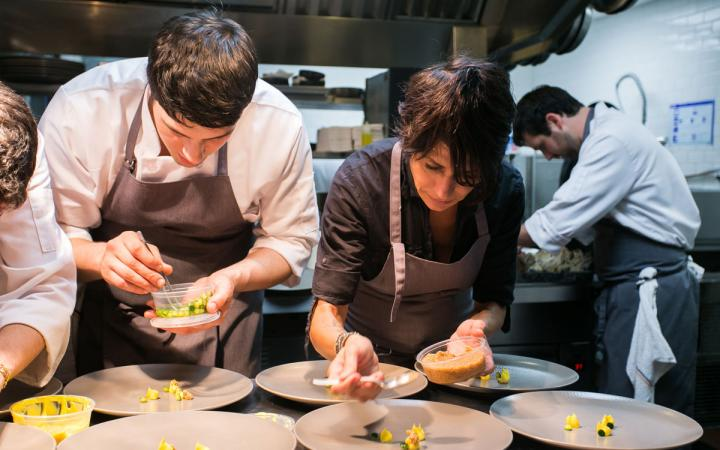 Chef Dominique Crenn helps one of her chefs plate a dish at Atelier Crenn restaurant in San Francisco.