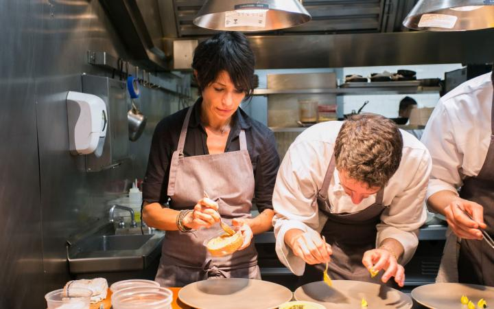 Chef Dominique Crenn assists one of her talented cooks with a dish at Atelier Crenn in San Francisco.