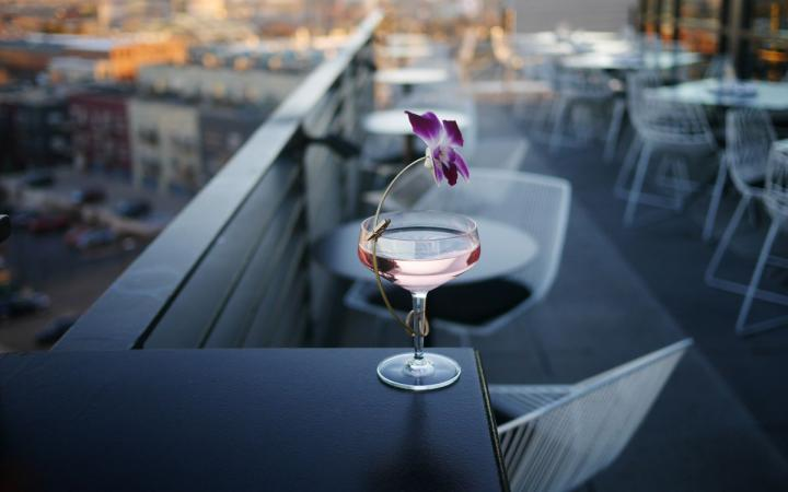 Pink cocktail with flower against a skyline.