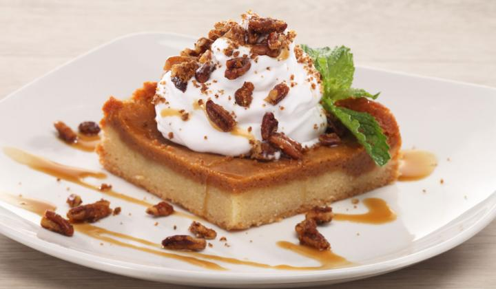 Ooey Gooey Pumpkin Spice Butter Cake topped with spiced pecans and vanilla whipped cream, drizzled with Woodford Reserve-spiked salted caramel sauce