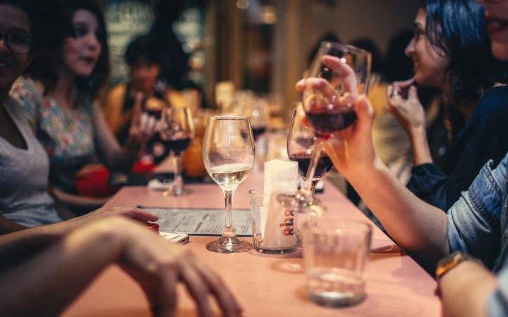 Diners share wine around a restaurant table.