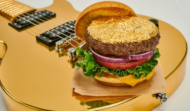 A half-pound fresh steakburger topped with 24-Karat edible gold leaf on a guitar at Hard Rock Cafe.