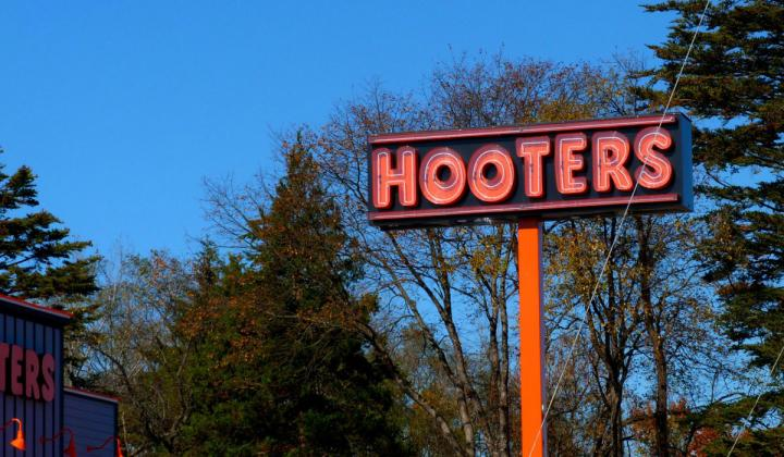 The Hooters sign stands tall, showcasing the famous logo of the restaurant chain.