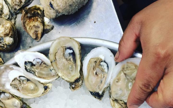Oysters on ice and a hand shucking