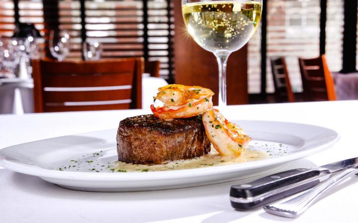 Steak and lobster, served with a glass of white wine at Ocean Prime restaurant.