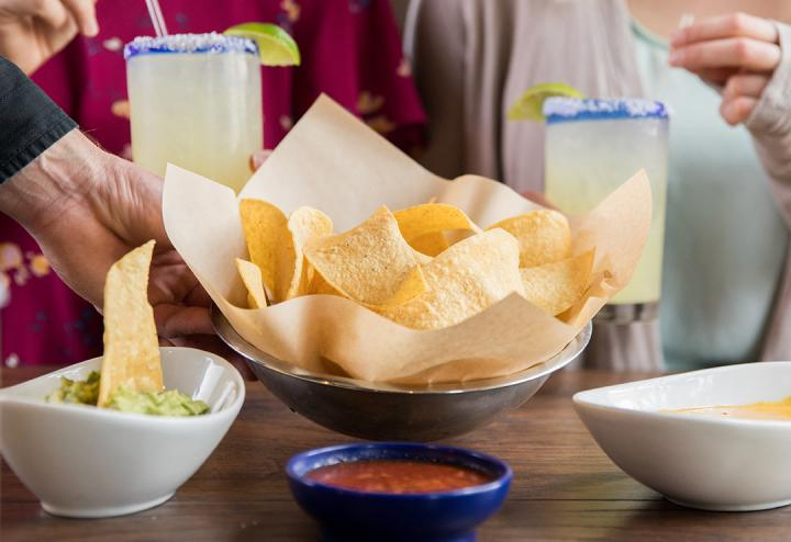 Chips being placed in front of 2 margaritas