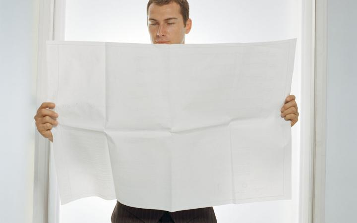 Man holding up large piece of paper.