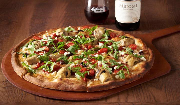 A pizza pie with a bottle of wine in the background.