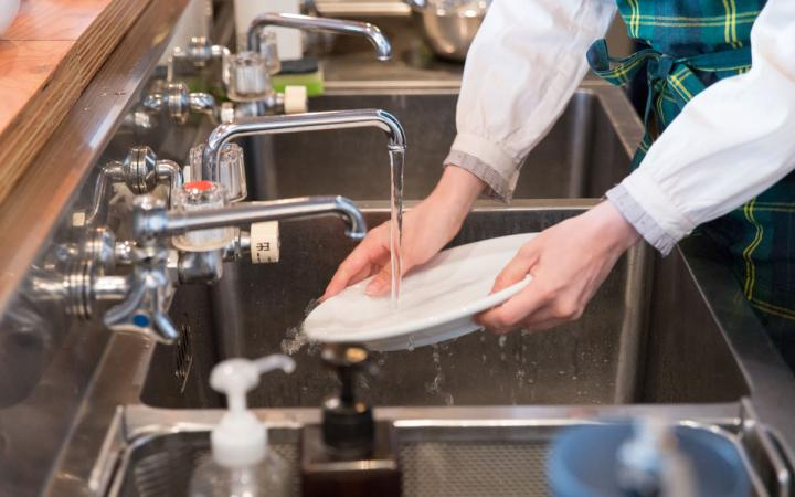 A restaurant employee washes dishes.