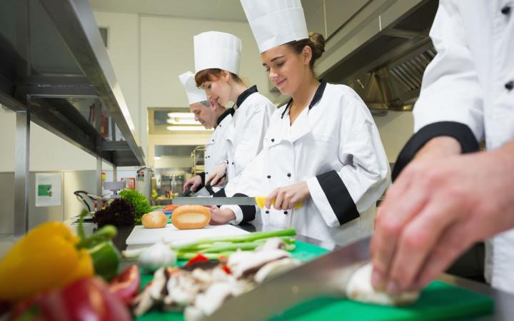 Four chefs preparing food at counter in a row.