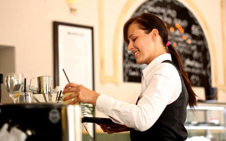 A waitress brings back a drink at a restaurant.