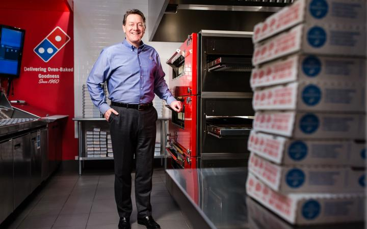 Domino's CEO J. Patrick Doyle stands among a backdrop of pizza boxes. He's leaving the company in June.