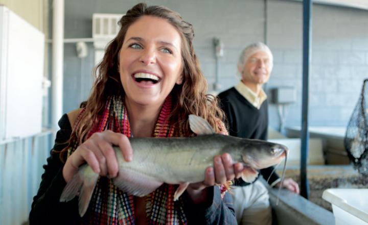 Chef Vivian Howard laughs while holding a fish.