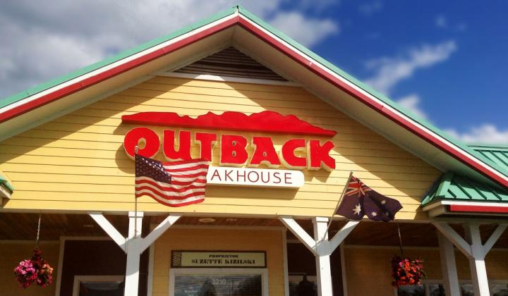 Outback Steakhouse with the American flag blowing outside.