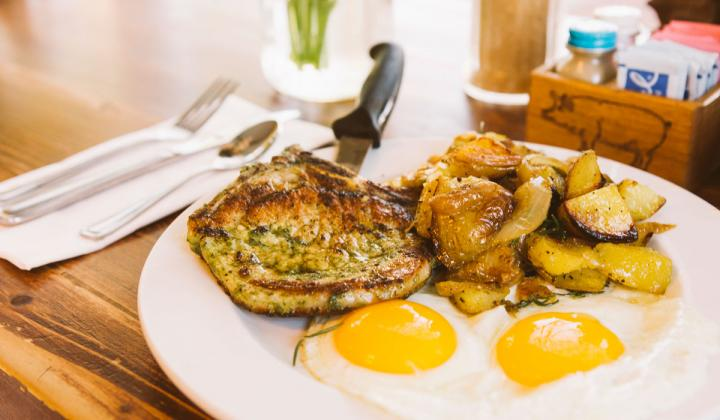 Chop & Chick, a giant Iowa pork rib chop marinated in tangy pesto sauce, and served with two eggs.