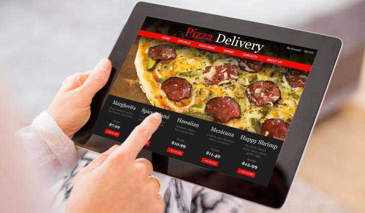 Woman ordering pizza online from a tablet.