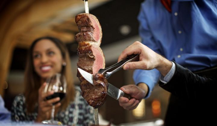 Fogo de Chão's meat is sliced off a skewer in front of guests.