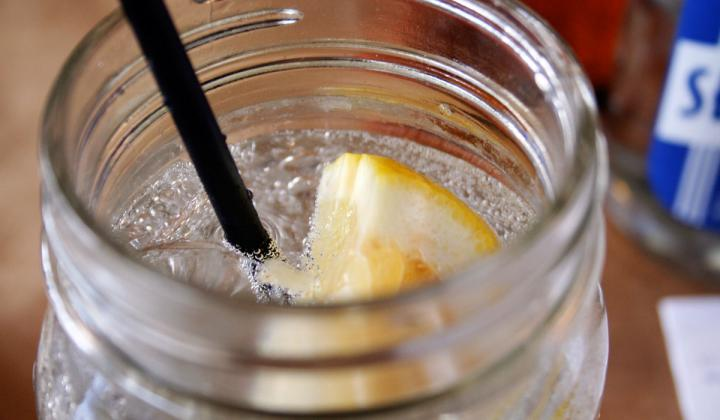 Sparkling water with lemon in a mason jar.