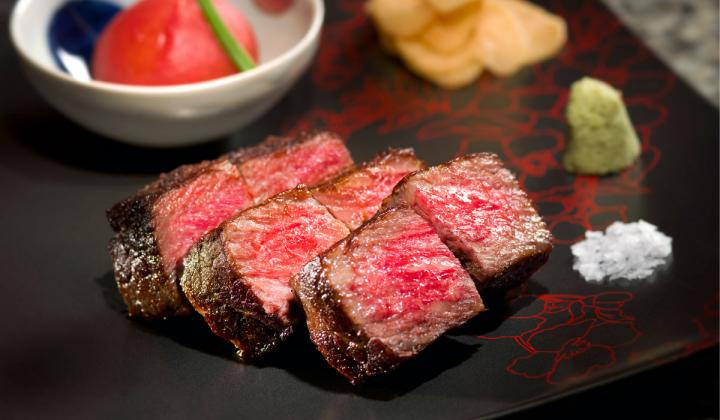 Waygu beef is cut into strips and presented medium rare.