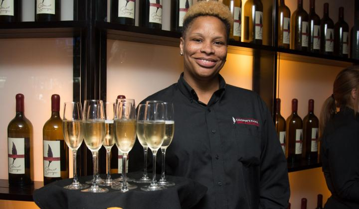 Employee holds a tray at Cooper's Hawk Winery & Restaurants.