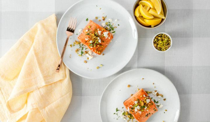 Two plates of salmon on a white table.