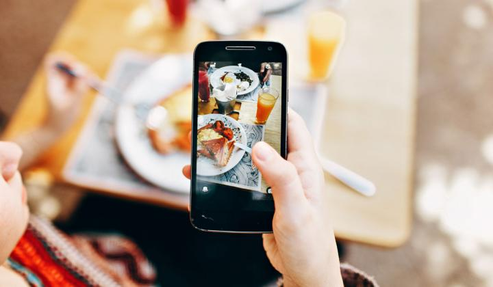 A woman takes a photo of food at a restaurant with her phone.