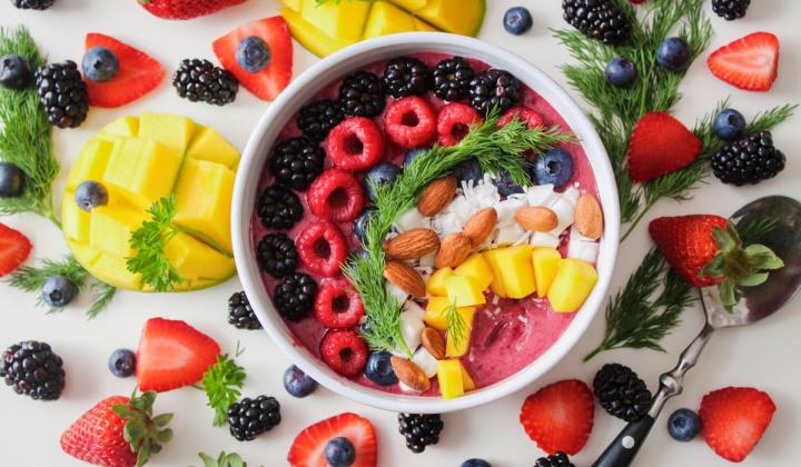 A top view of a bowl with fresh dessert and berries.
