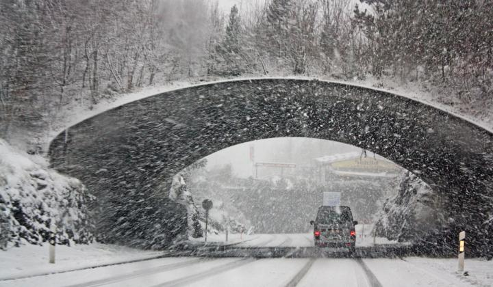 A car drives under a bridge in a snow storm.