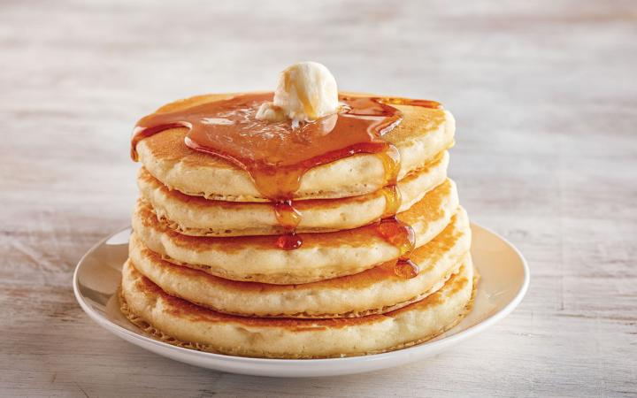 A stack of pancakes with butter and syrup at IHOP.
