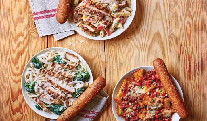 Three plates of Applebee's new Neighborhood Pasta bowls and breadsticks.