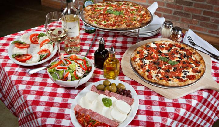 A table of pizza and sides at Grimaldi's Pizzeria.