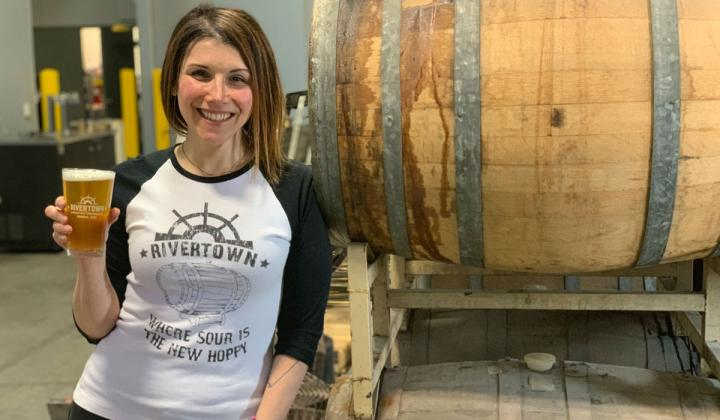 Lindsey Roeper of Rivertown Brewery & Barrel House holds a beer.