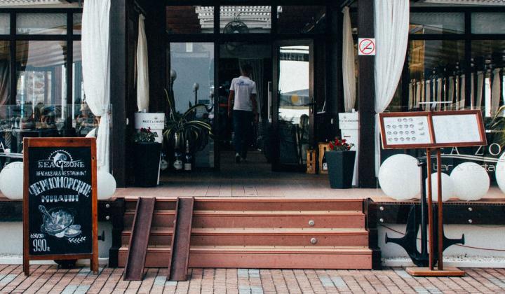 A man walks through the entrance of a restaurant.