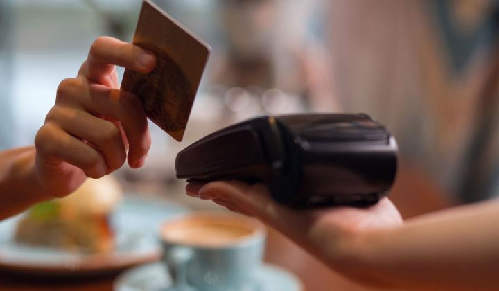 A customer pays by swiping their card at a restaurant.