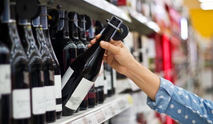 Woman is buying a bottle of wine at the supermarket background.