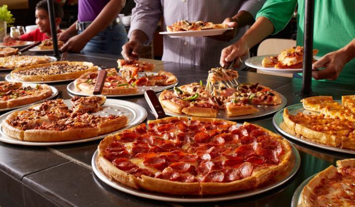 Guests grab pizza at Pizza Inn's buffet.