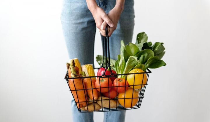 A woman carries a basket of vegetables.