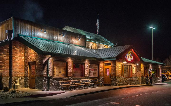 A Texas Roadhouse shines brightly at night. The famous steakhouse is always popular with loyal customers.