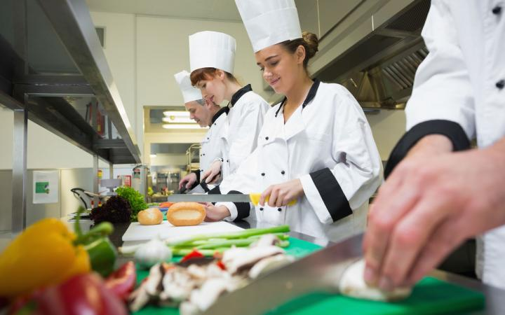 A female chef chops food in a restaurant with other chefs.