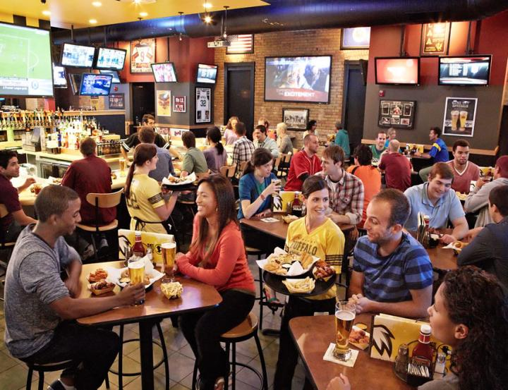A rowdy Buffalo Wild Wings restaurant is seen in the background, with sports fans and guests grabbing some beers and wings.