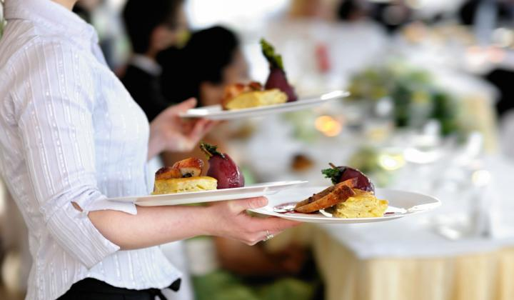 A waitress carries three plates of food.