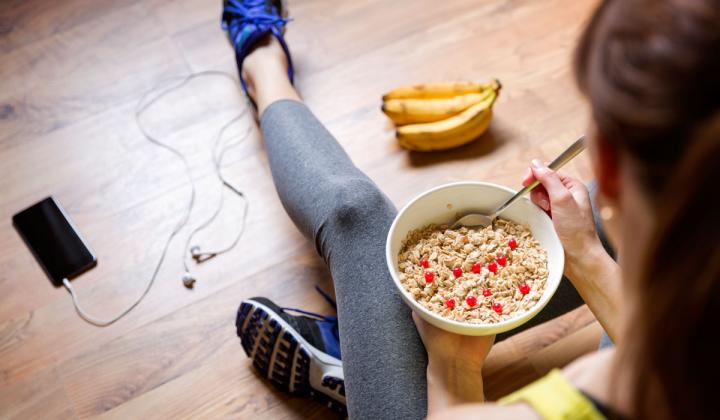 After a workout, a woman eats a bowl of food while listening to her phone.