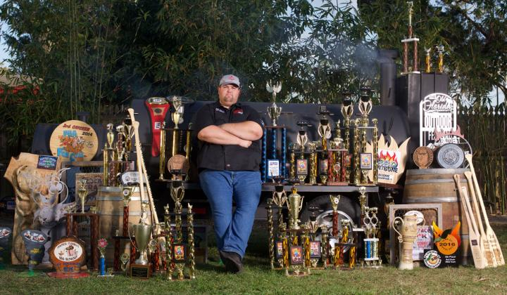 Sonny's BBQ's Head Pitmaster Bryan Mroczka stands with all his trophies.
